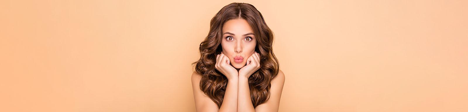 Female sending kiss pout lips over beige pastel color background